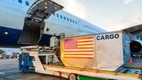 Container mit US-Flagge wartet vor der Frachtklappe eines Flugzeugs