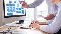 Ein Mensch zeigt auf ein Organigramm auf einem Bildschirm, eine Frau sitzt an der Tastatur davor