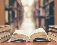 Mehrere Bücher vor langen Regalen, eines aufgeschlagen