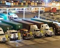LKW an einem Checkpoint im Hafen, im Hintergrund Container