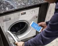 Mann steuert Waschmaschine mit Smartphone