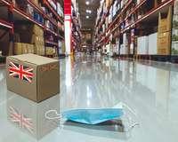 Päckchen mit UK-Flagge und Corona-Maske liegen auf dem Boden eines Warenlagers