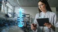 Ingenieurin mit Tablet betrachtet das Hologramm eines Maschinen-Bauteils
