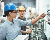 Arbeiterin erklärt jüngerem Kollegen eine Maschine