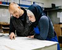 Mann erklärt Frau mit Kopftuch einen Bauplan